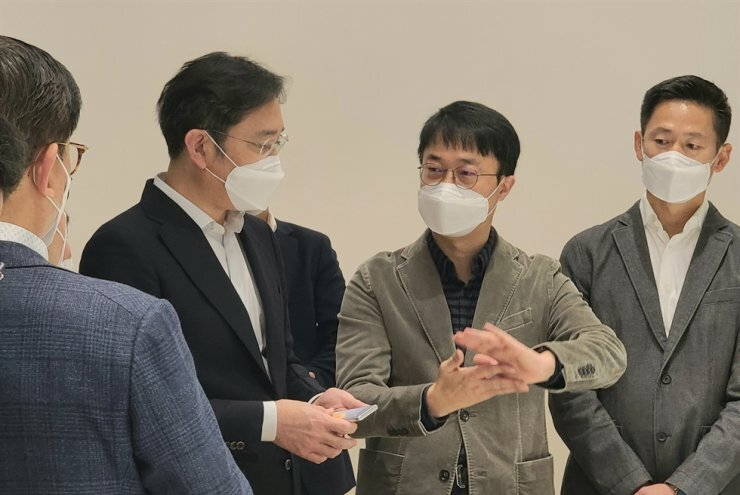 El vicepresidente Lee Jae-yong con el supuesto prototipo de teléfono enrollable hablando con los investigadores de Samsung: ¿Podríamos ver una línea Galaxy Roll o Slide este año? Consejos sobre la pantalla Samsung, así que ...